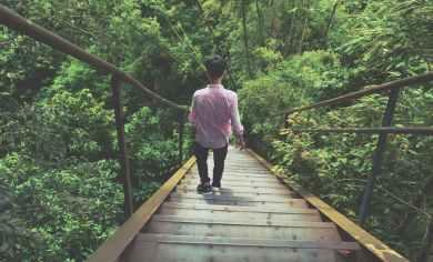 man wearing pink dress shirt walking through stairs